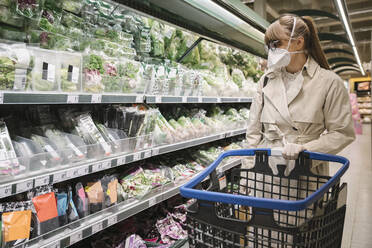 Woman with face mask and disposable gloves in a supermarket - AHSF02600