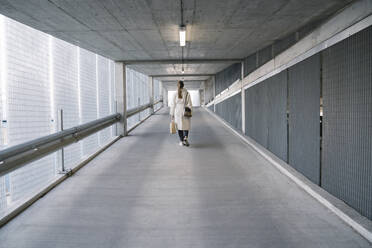Rear view of woman walking in corridor of a car park after shopping - AHSF02606