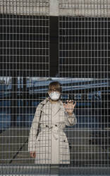 Woman wearing face mask standing behind grating in a car park - AHSF02609