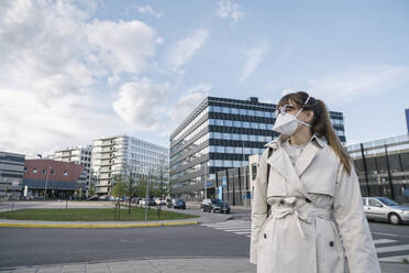Woman wearing face mask walking in the city - AHSF02612