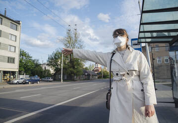 Woman wearing face mask in the city hailing a taxi - AHSF02615