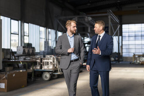 Two businessmen walking and talking in a factory - DIGF10990
