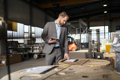 Young businessman with tablet in a factory - DIGF11038