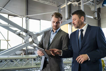 Two businessmen with tablet having a meeting in a factory - DIGF11062