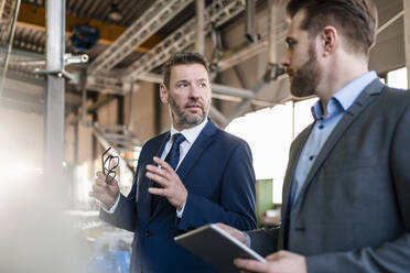 Two businessmen with tablet having a meeting in a factory - DIGF11071