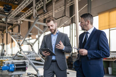 Two businessmen with tablet having a meeting in a factory - DIGF11074