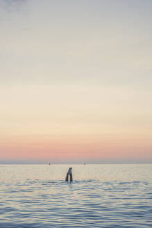 Feet of teenage girl diving in the sea at sunrise - FVSF00309