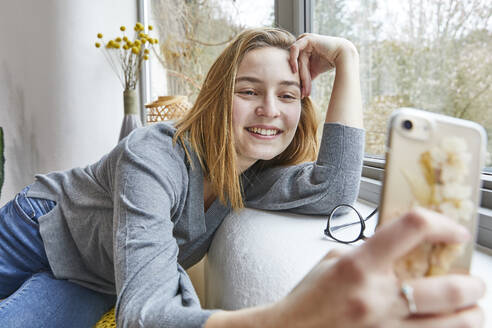 Portrait of smiling young woman leaning on window sill at home taking selfie with smartphone - FSF01081
