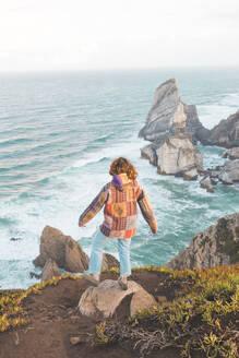 Young woman standing on rock at Ursa Beach, Lisboa Region, Portugal - FVSF00338
