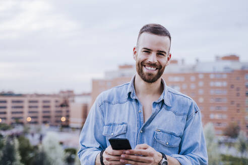 Portrait of relaxed young man with smartphone outdoors - EBBF00124