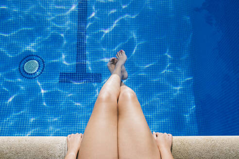 Young woman with feet in water relaxing at poolside - ABZF03131