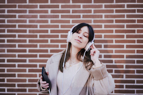 Portrait of woman with eyes closed listening music with headphones and smartphone in front of brick wall - EBBF00164