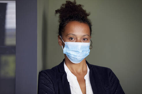 Portrait of businesswoman wearing light blue protective mask - RBF07686