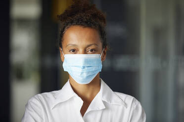 Portrait of businesswoman wearing light blue protective mask - RBF07689