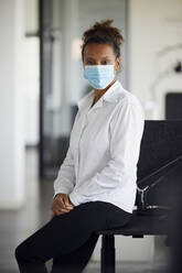 Portrait of businesswoman wearing light blue protective mask - RBF07692