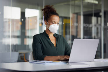 Portrait of businesswoman wearing protective mask working on laptop at counter - RBF07707