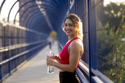 Smiling female athlete holding water bottle while standing on covered bridge in city - OCMF01251