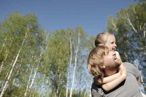 Happy father piggybacking daughter against trees in park during sunny day - EYAF01059