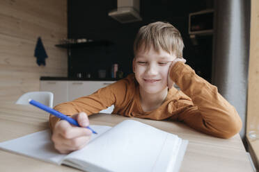 Smiling boy sitting at table writing into booklet at home - EYAF01068