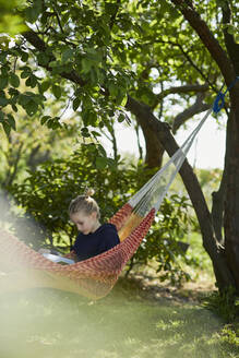 Girl in hammock reading a book - MCF00835