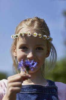Portrait of girl wearing daisy wreath holding a flower - MCF00886