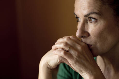 Thoughtful lonely mature woman looking away at home during curfew - FLLF00490