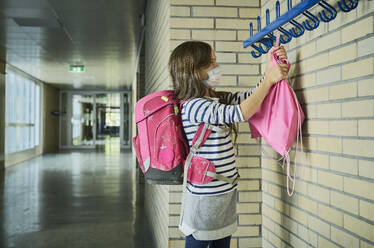 Girl wearing mask in school hanging up pouch - DIKF00502