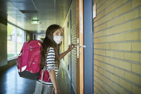 Girl wearing mask in school opening classroom door - DIKF00505