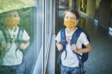 Boy wearing mask in school mirrored in window - DIKF00508
