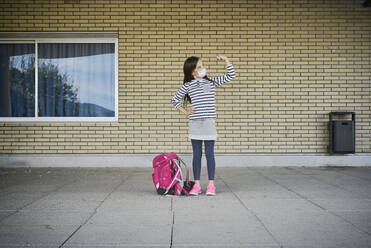 Girl with schoolbag wearing mask standing in front of building flexing her muscles - DIKF00523