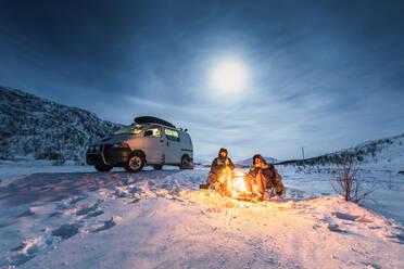 Campers at camp fire in winter landscape in polar night, Kilpisjaervi, Enontekioe, Finland - WVF01531