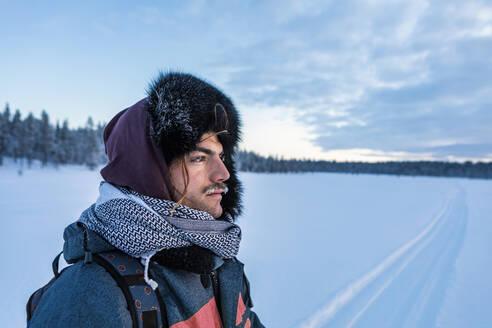 Portrait of man in winter landscape with frozen moustache, Ounasjaervi, Enontekioe, Finland - WVF01552