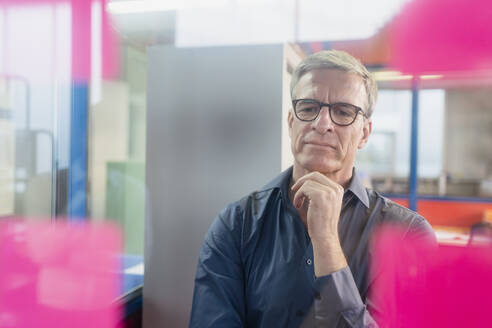 Thoughtful mature male entrepreneur looking at adhesive notes on glass in office - DIGF11282