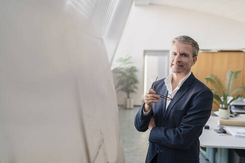 Portrait of smiling male entrepreneur holding eyeglasses while standing by whiteboard in office - DIGF11285