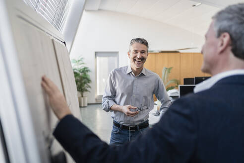 Happy handsome businessman discussing strategy over whiteboard with male colleague in meeting at office - DIGF11291