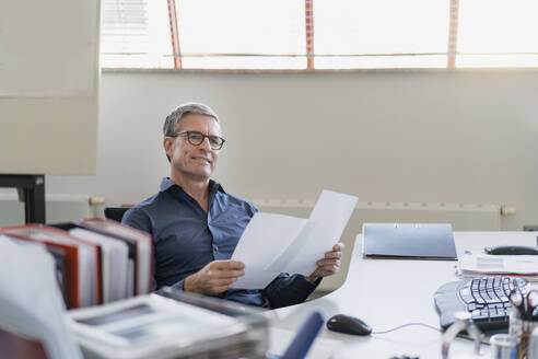 Thoughtful mature businessman looking away while sitting with papers at desk in office - DIGF11306