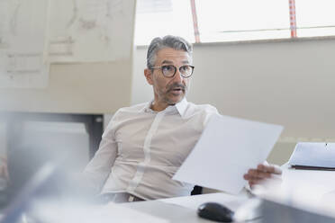 Confident businessman looking away with raised eyebrows while sitting with document at desk in office - DIGF11312