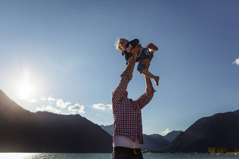 Father holding aloft daughter against blue sky at Achensee, Tyrol State, Austria - JLOF00397