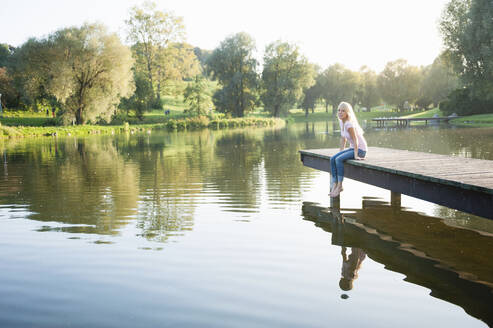 Young woman sitting on pier over lake in park during sunset - DIGF11385
