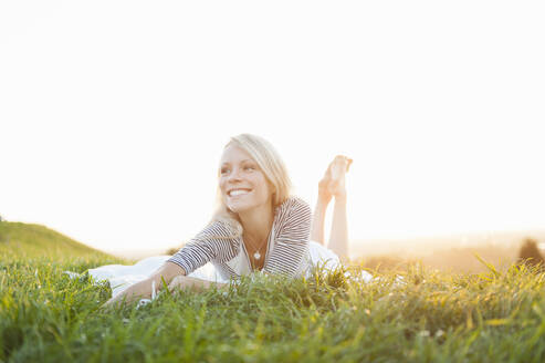 Happy thoughtful young woman lying on grassy land against clear sky in park during sunset - DIGF11388