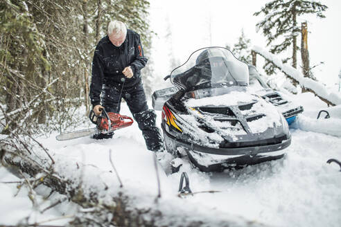 Retired man using chainsaw to clear trails while snowmobiling. - CAVF82032