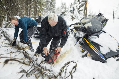 Elderly man and son using chainsaw to clear trails while snowmobiling. - CAVF82035