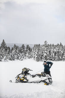 Snowmobiler uses pull cord to start his machine in winter conditions. - CAVF82038