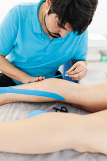 Visually impaired physiotherapist applying Kinesio tape on boy's leg in clinic - MRRF00062