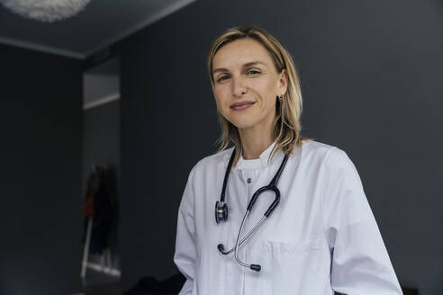 Portrait of doctor with stethoscope against grey background - MFF05619