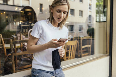 Woman with protective mask in her hand looking at smartphone in front of a closed coffee shop - MFF05637