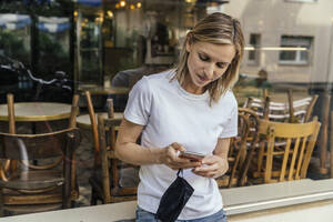 Portrait of woman with protective mask in her hand text messaging in front of a closed coffee shop - MFF05640