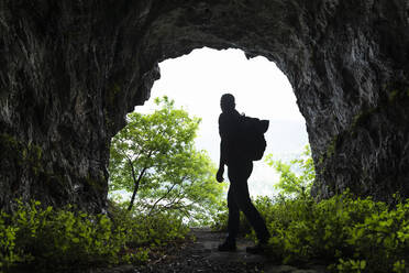 Mature male hiker walking while exploring cave - MCVF00393