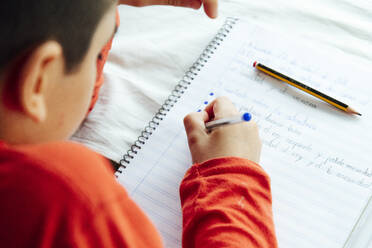 Young boy writing in book with pen during homeschooling - JCMF00761