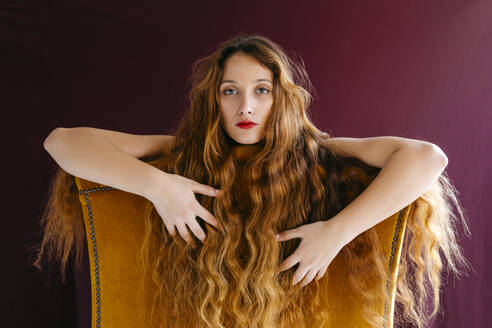 Portrait of confident young woman with long brown wavy hair leaning on chair against colored background - TCEF00707